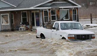 Flood waters surround a pickup and a home Friday, Feb. 21, 2014, on Barton Beach Road in Lafayette, Ind.  Authorities say an ice jam has caused a creek near Lafayette to overflow its banks, flooding several homes and prompting some evacuations. (AP Photo/Journal & Courier, John Terhune)