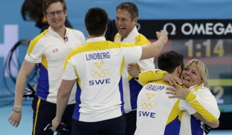 Sweden's Sebastian Kraup hugs coach Eva Lund, far right, while celebrating their victory over China in the men's curling bronze medal game at the 2014 Winter Olympics, Friday, Feb. 21, 2014, in Sochi, Russia. (AP Photo/Robert F. Bukaty)