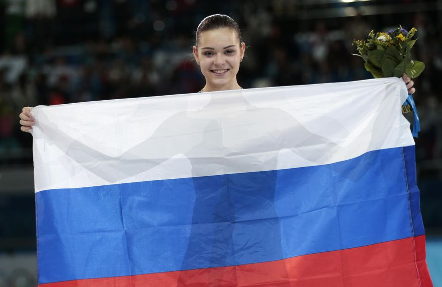 Adelina Sotnikova of Russia celebrates after placing first during the flower ceremony for the women's free skate figure skating final at the Iceberg Skating Palace during the 2014 Winter Olympics, Thursday, Feb. 20, 2014, in Sochi, Russia. Sotnikova placed first, followed by Kim and Kostner. (AP Photo/Ivan Sekretarev)