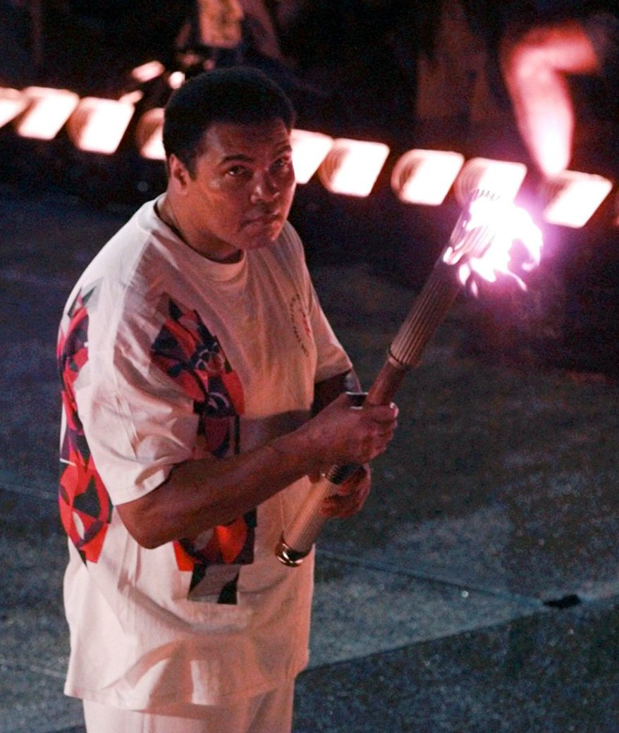 ADVANCE FOR USE SUNDAY, FEB. 23, 2014 AND THEREAFTER - FILE - In this Friday, July 19, 1996 file photo, Muhammad Ali holds a torch as he watches as the flame climb up to the Olympic cauldron during the opening ceremonies of the Summer Olympics in Atlanta. (AP Photo/Doug Mills)