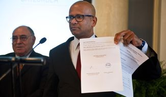 Ram Manikkalingam, a member of the commission overseeing the Basque group ETA's ceasefire, announced in 2011, right, shows a document from ETA after the armed group announced a first step in disarmament, putting some weapons and explosives out of use, in Bilbao northern Spain, Friday, Feb. 21, 2014. ETA is blamed for killing some 830 people between the late 1960s in bombings and its 2011 cease-fire in a campaign for a Basque homeland in northern Spain and southwest France. (AP Photo/Alvaro Barrientos)