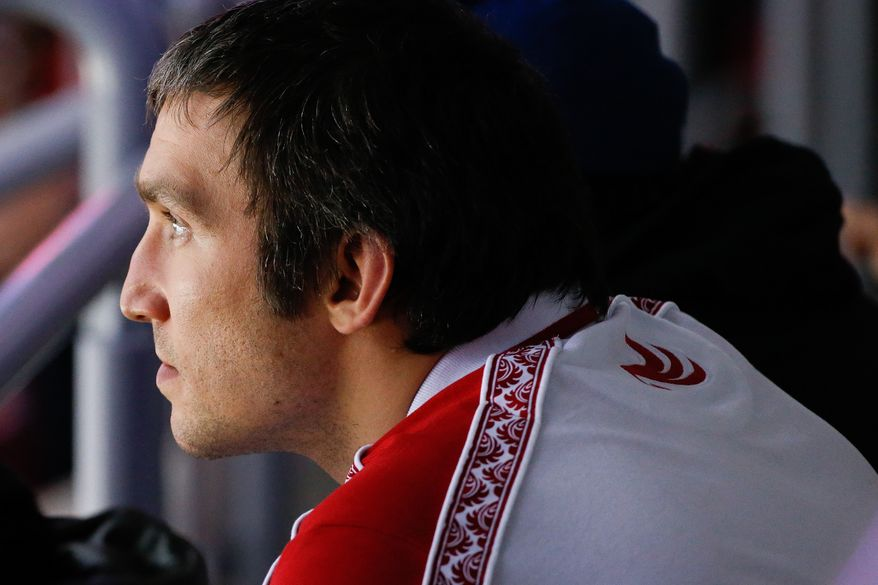 Russia forward Alexander Ovechkin watches the start of the men's semifinal ice hockey game between Canada and the United States at the 2014 Winter Olympics, Friday, Feb. 21, 2014, in Sochi, Russia. (AP Photo/Mark Humphrey)