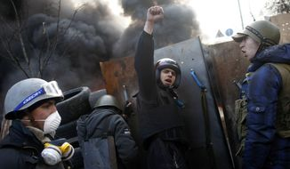 "Anti-government protesters shout ""Glory to the Ukraine"" as they man a barricade at Independence Square in Kiev, Ukraine, Friday, Feb. 21, 2014. Ukraine's presidency said Friday that it has negotiated a deal intended to end battles between police and protesters that have killed scores and injured hundreds, but European mediators involved in the talks wouldn't confirm a breakthrough. (AP Photo/ Marko Drobnjakovic)"