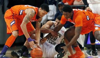 Georgia Tech guard Corey Heyward (30) battles with Clemson's K.J. McDaniels (32), left, and Josh Smith (33) for a loose ball in the first  half of an NCAA college basketball game  Saturday, Feb. 22, 2014, in Atlanta. (AP Photo/John Bazemore)