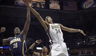Milwaukee Bucks guard Giannis Antetokounmpo (34) goes up for a basket against the defense of Indiana Pacers center Ian Mahinmi (28) during the first half of an NBA basketball game Saturday, Feb. 22, 2014, in Milwaukee. (AP Photo/Darren Hauck)