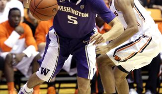 Washington guard Nigel Williams-Goss, left, drives to the hoop past Oregon State guard Hallice  Cooke during the first half of an NCAA basketball game in Corvallis, Ore., Saturday, Feb. 22, 2014.(AP Photo/Don Ryan)