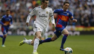 Real Madrid's Gareth Bale, left, in action with Elche's Edu Albacar, right, during a Spanish La Liga soccer match between Real Madrid and Elche at the Santiago Bernabeu stadium in Madrid, Spain, Saturday, Feb. 22, 2014. (AP Photo/Andres Kudacki)