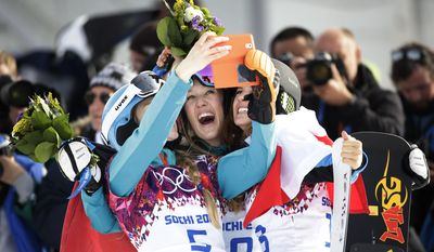 Bronze medalist Amelie Kober, from left, of Germany silver medalist Anke Karstens, also of Germany,and gold medalist Julia Dujmovits, of Austria, take pictures after their flower ceremony for the women's snowboard parallel slalom at the Rosa Khutor Extreme Park, at the 2014 Winter Olympics, Saturday, Feb. 22, 2014, in Krasnaya Polyana, Russia. (AP Photo/Jae C. Hong)