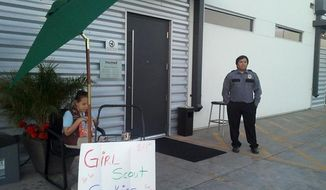 ** FILE ** Lexi Menees, 8, sells Girl Scout Cookies while sitting outside Trumed Dispensary, which sells medical marijuana for licensed patients, in Phoenix on Friday, Feb. 21, 2014. (AP Photo/Terry Tang)