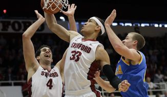 Stanford forward Dwight Powell (33) grabs a rebound next to teammate Stefan Nastic (4) and UCLA forward Travis Wear during the first half of an NCAA college basketball game on Saturday, Feb. 22, 2014, in Stanford, Calif. (AP Photo/Marcio Jose Sanchez)