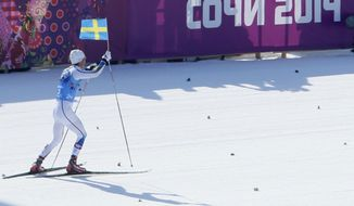 Sweden's Marcus Hellner skis with the Swedish flag as his team win the gold during the men's 4x10K cross-country relay at the 2014 Winter Olympics, Sunday, Feb. 16, 2014, in Krasnaya Polyana, Russia. (AP Photo/Dmitry Lovetsky)