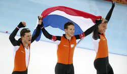 Speedskaters from the Netherlands, left to right, Sven Kramer, Jan Blokhuijsen and Koen Verweij hold their national flag and celebrate winning gold in the men's team pursuit at the Adler Arena Skating Center at the 2014 Winter Olympics, Saturday, Feb. 22, 2014, in Sochi, Russia. (AP Photo/Pavel Golovkin)
