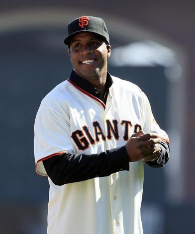 FILE - This Oct. 19, 2010, file photo shows former San Francisco Giants Barry Bonds acknowledging the crowd before throwing out a ceremonial first pitch before Game 3 of baseball's National League Championship Series against the Philadelphia Phillies, in San Francisco. Bonds is returning to the Giants as a spring training instructor. The Giants say Bonds is expected to arrive during the second week of March 2014. (AP Photo/Jeff Chiu, File)