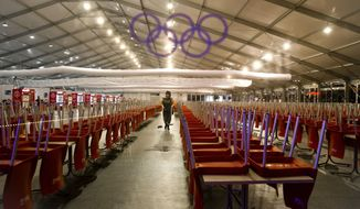 Seen through a plastic sheet with the Olympic ring logo, a woman cleans a large food court in the Olympic park during the 2014 Winter Olympics, early Saturday, Feb. 22, 2014, in Sochi, Russia. (AP Photo/Vadim Ghirda)