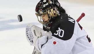 Goalkeeper Nana Fujimoto of Japan blocks a shot on goal during the second period of the 2014 Winter Olympics women's ice hockey game against Germany at Shayba Arena, Tuesday, Feb. 18, 2014, in Sochi, Russia. (AP Photo/Petr David Josek)