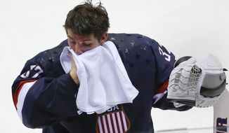 Goalkeeper Jonathan Quick of the United States wipes his face during a break in the action against Finland in the men's bronze medal ice hockey game at the 2014 Winter Olympics, Saturday, Feb. 22, 2014, in Sochi, Russia. (AP Photo/Julio Cortez)
