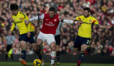 Arsenal's Lukas Podolski, fights for the ball with Sunderland's Ki Sung-Yong (left) and Phillip Bardsley, during their English Premier League soccer match, at Emirates Stadium, in London, Saturday, Feb. 22, 2014. (AP Photo/Bogdan Maran)