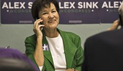 FILE - In this Nov. 23, 2013 file photo, Florida Democratic Congressional candidate Alex Sink works the phone in Clearwater, Fla. Obamacare is on the ballot in a big way in a competitive House race in Florida that offers a preview of the nationwide campaign for Congress this fall. (AP Photo/Steve Nesius, File)
