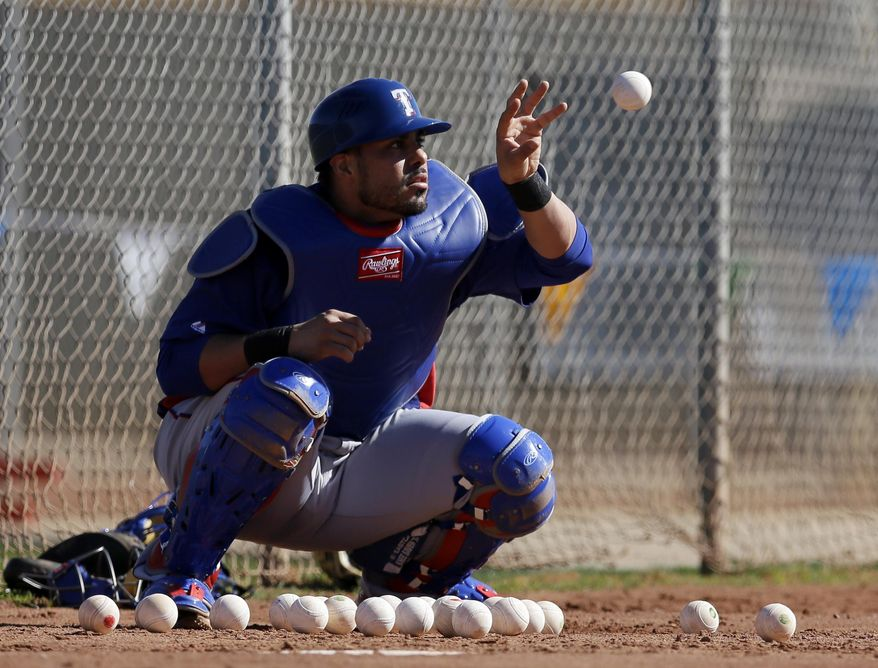 Texas Rangers catcher Geovany Soto takes throws bare handed in the bullpen as he warms up during spring training baseball practice, Monday, Feb. 17, 2014, in Surprise, Ariz. (AP Photo/Tony Gutierrez)