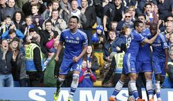 Chelsea's captain John Terry, left, celebrates with teammates after scoring against Everton during an English Premier League soccer match at the Stamford Bridge ground in London, Saturday, Feb. 22, 2014. Chelsea won the match 1-0. (AP Photo / Lefteris Pitarakis)