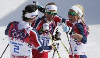 Norway's gold medal winner Marit Bjoergen, left,  congratulates Norway's bronze medal winner Kristin Stoermer Steira and Norway's silver medal winnerTherese Johaug, right, after the women's 30K cross-country race at the 2014 Winter Olympics, Saturday, Feb. 22, 2014, in Krasnaya Polyana, Russia. (AP Photo/Matthias Schrader)