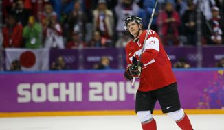 Canada forward Sidney Crosby raises his stick to hockey fans after Canada beat the USA 1-0 in a men's semifinal ice hockey game at the 2014 Winter Olympics, Friday, Feb. 21, 2014, in Sochi, Russia. (AP Photo/Julio Cortez)
