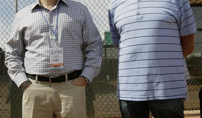 Milwaukee Brewers owner Mark Attanasio, left, and Bob Uecker watch a spring training baseball practice, Saturday, Feb. 22, 2014, in Phoenix. (AP Photo/Rick Scuteri)