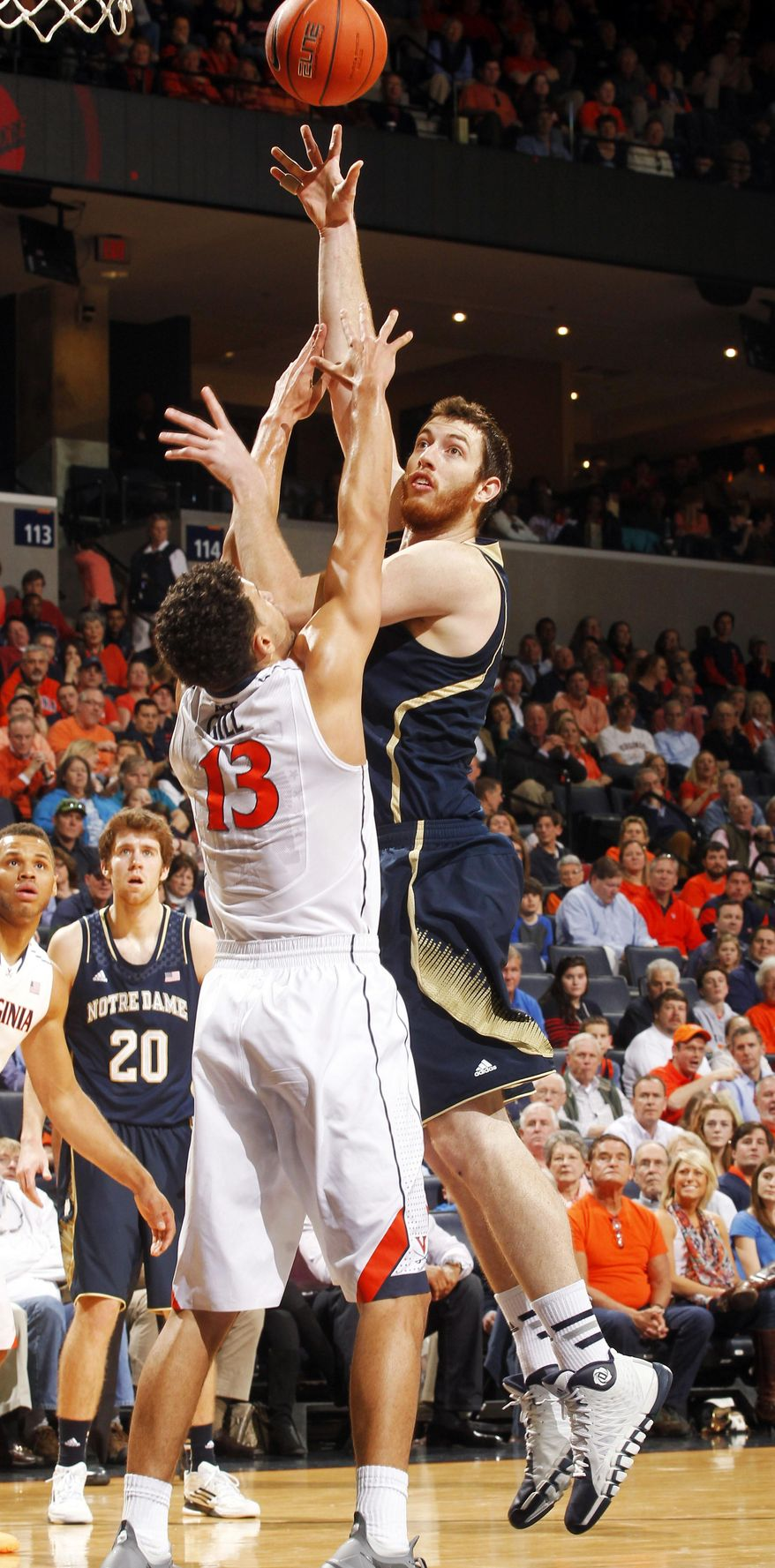 Notre Dame center Garrick Sherman, right, shoots over Anthony Gill during an NCAA college basketball game Saturday, Feb. 22, 2014, in Charlottesville, Va. (AP Photo/Andrew Shurtleff)