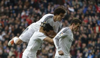 Real's Gareth Bale, right, celebrates his goal with teammates during a Spanish La Liga soccer match between Real Madrid and Elche at the Santiago Bernabeu stadium in Madrid, Spain, Saturday, Feb. 22, 2014. (AP Photo/Andres Kudacki)