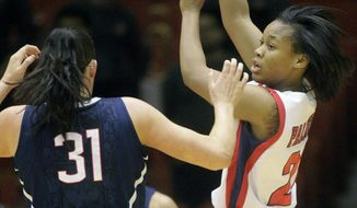 CORRECTS TO  AN NCAA GAME Houston guard Jessieka Palmer (21) passes the ball away from Connecticut center Stefanie Dolson (31) during the first half of an NCAA women's basketball game, Saturday, Feb. 22, 2014, in Houston. (AP Photo/Patric Schneider)