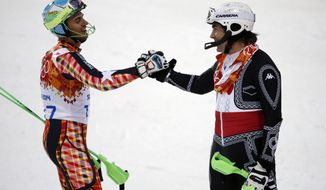 Mexico's Hubertus von Hohenlohe, right, and East Timor's Yohan Goncalves Goutt shake hands after von Hohenlohe crashed during first run of the men's slalom at the Sochi 2014 Winter Olympics, Saturday, Feb. 22, 2014, in Krasnaya Polyana, Russia. (AP Photo/Christophe Ena)