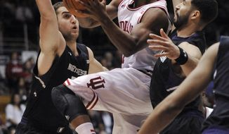 Indiana's Kevin Yogi Ferrell,(11) goes up for a shot against Northwestern's Alex Olah, left, and Drew Crawford (1) during the first half of an NCAA college basketball game in Evanston, Ill., Saturday, Feb. 22, 2014. (AP Photo/Paul Beaty)