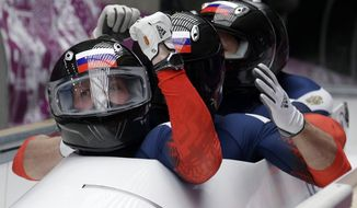 The team from Russia RUS-1, with Alexander Zubkov, Alexey Negodaylo, Dmitry Trunenkov, and Alexey Voevoda, brake in the finish area after tenor second run during the men's four-man bobsled competition at the 2014 Winter Olympics, Saturday, Feb. 22, 2014, in Krasnaya Polyana, Russia. (AP Photo/Michael Sohn)