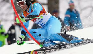 Slovenia's Tina Maze skis past a gate in the first run of the women's slalom at the Sochi 2014 Winter Olympics, Friday, Feb. 21, 2014, in Krasnaya Polyana, Russia. (AP Photo/Alessandro Trovati)