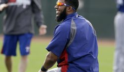 Texas Rangers' Elvis Andrus laughs with teammates as they stretch before a morning workout during spring training baseball practice, Wednesday, Feb. 19, 2014, in Surprise, Ariz. (AP Photo/Tony Gutierrez)