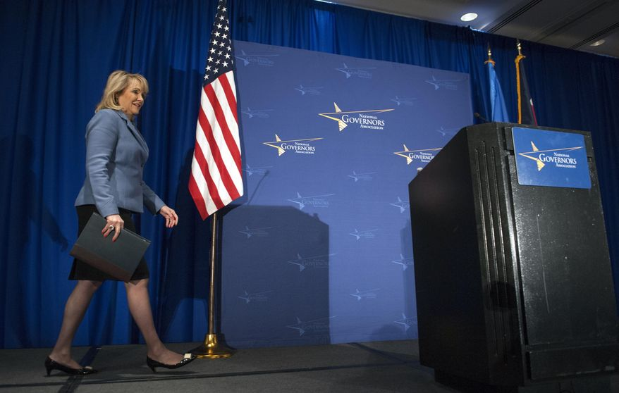 National Governor's Association chair Oklahoma Gov. Mary Fallin walks onstage to meet with the media during the NGA's Winter Meeting in Washington, Saturday, Feb. 22, 2014. (AP Photo/Cliff Owen)