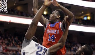 St. John's Jakarr Sampson, center, puts up the shot over Villanova's Daniel Ochefu, left, with St. John's Sir'Dominic Pointer along side them during the first half of an NCAA college basketball game, Saturday, Feb. 22, 2014, in Philadelphia. (AP Photo/Chris Szagola)