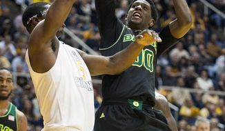 Baylor's Royce O'Neale, right, looks to shoot as West Virginia's Devin Williams defends during the first half of an NCAA college basketball game Saturday, Feb. 22, 2014, in Morgantown, W.Va. (AP Photo/Andrew Ferguson)