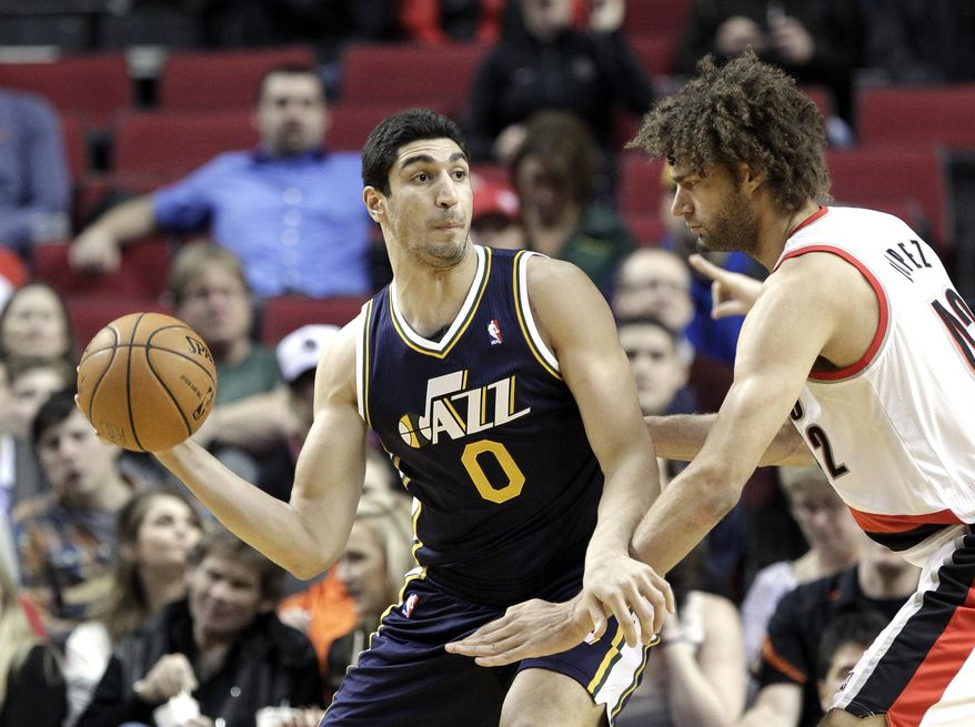 Utah Jazz center Enes Kanter, left, looks to pass against Portland Trail Blazers center Robin Lopez during the first half of an NBA basketball game in Portland, Ore., Friday, Feb. 21, 2014. (AP Photo/Don Ryan)