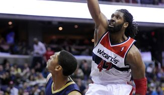 Washington Wizards forward Nene (42), of Brazil, dunks over New Orleans Pelicans forward Anthony Davis (23) during the second half of an NBA basketball game, Saturday, Feb. 22, 2014, in Washington. The Wizards won 94-93. (AP Photo/Nick Wass)