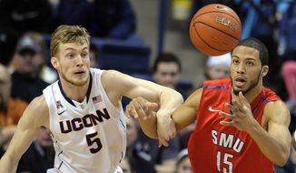 Connecticut's Niels Giffey (5) and SMU's Cannen Cunningham (15) fight for the loose ball during the first half of an NCAA college basketball game in Storrs, Conn., Sunday, Feb. 23, 2014. (AP Photo/Fred Beckham)