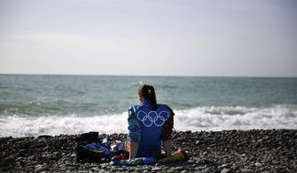 An Olympic volunteer sits on the beach along the Black Sea ahead of tonight's 2014 Winter Olympics closing ceremony, Sunday, Feb. 23, 2014, in Sochi, Russia. (AP Photo/David Goldman)