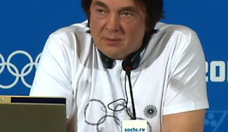 Konstantin Ernst, chief creative director of the opening and closing ceremonies for the 2014 Winter Olympics in Sochi, wears a T-shirt with the Olympic rings where one of the five rings is a snowflake during a news conference on the last day of the Olympics in Sochi, Russia, Sunday, Feb. 23, 2014. The T-shirt is a reference to the opening ceremony, when five snowflakes were supposed to open up into the five Olympic rings, but one failed to open. Ernst was met with applause and laughter when he took off his jumper at the press conference, revealing the T-shirt with the glitch. (AP Photo/Dorothee Thiesing)