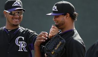 Colorado Rockies starting pitcher Jhoulys Chacin, left, pulls on the beard of invitee pitcher Manuel Corpas during baseball spring training Friday, Feb. 21, 2014, in Scottsdale, Ariz. (AP Photo/Gregory Bull)