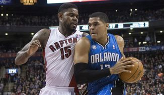 Orlando Magic's Tobias Harris, right, drives at Toronto Raptors' Amir Johnson during the first half of an NBA basketball game in Toronto, Sunday, Feb. 23, 2014. (AP Photo/The Canadian Press, Chris Young)