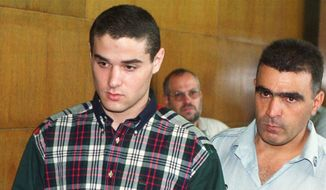 File - In this July 5, 1999 file photo, Samuel Sheinbein, accused of the 1997 murder of Alfredo Tello Jr., in Maryland, is brought in handcuffs to a Tel Aviv court.  Israeli special forces raided a prison in central Israel on Sunday, killing one of the country's most notorious inmates after he seized a guard's weapon, shot three guards and barricaded himself inside the compound. Police identified the inmate as Samuel Sheinbein, an American who fled to Israel after committing a gruesome murder in Maryland in 1997 and whose case sparked a high-profile row between the two allies.(AP Photo/Nati Harnik, File)