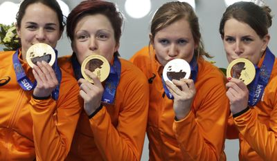 Gold medallists from team Netherlands, left to right, Marrit Leenstra, Jorien ter Mors, Lotte van Beek, and Ireen Wust kiss their medals during the medal ceremony for the women's team pursuit at the Adler Arena Skating Center at the 2014 Winter Olympics, Saturday, Feb. 22, 2014, in Sochi, Russia. (AP Photo/Matt Dunham)