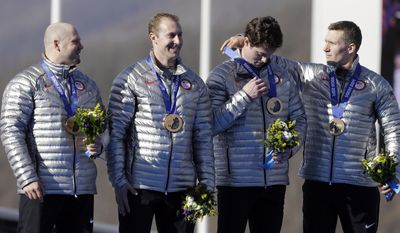 The United States' Christopher Fogt adjusts the medal of Steven Langton as they and driver Steven Holcomb, left, and Curtis Tomasevicz with USA-1  receive their bronze medals after the men's four-man bobsled competition final at the 2014 Winter Olympics, Sunday, Feb. 23, 2014, in Krasnaya Polyana, Russia.(AP Photo/Natacha Pisarenko)