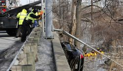 Workers remove a car from Otter Creek in Oregon, Ohio,  Sunday, Feb. 23, 2014. The Chevrolet Impala went through a guard rail on Otter Creek Road near Millard Avenue, into the creek below.  The female driver of the vehicle died in the accident.  (AP Photo/The Blade, Dave Zapotosky)