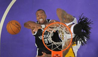 Brooklyn Nets center Jason Collins, left, battles for a rebound with Los Angeles Lakers' Jordan Hill during the first half of an NBA basketball game, Sunday, Feb. 23, 2014, in Los Angeles. (AP Photo/Mark J. Terrill)